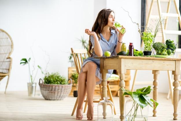 Piękna kobieta siedzi ze zdrową, zieloną żywnością i napojami w domu. wegański posiłek i koncepcja detoksykacji
