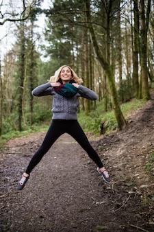 Piękna kobieta, skoki w lesie