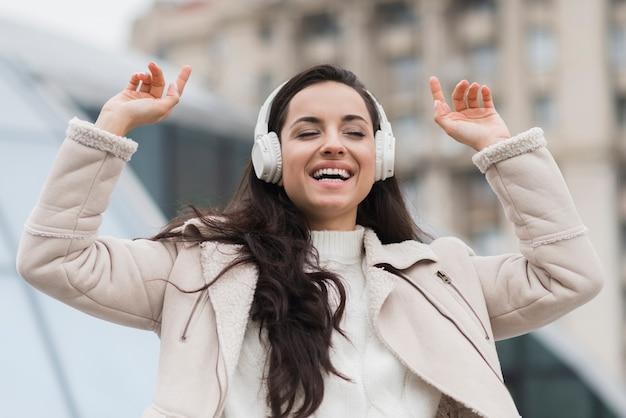 Piękna kobieta słucha muzyka na hełmofonach