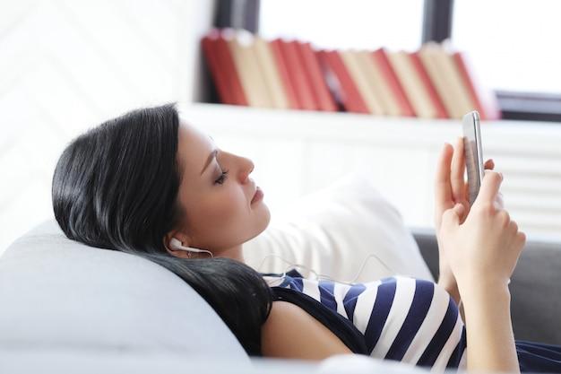 Piękna kobieta słucha muzyka z słuchawkami