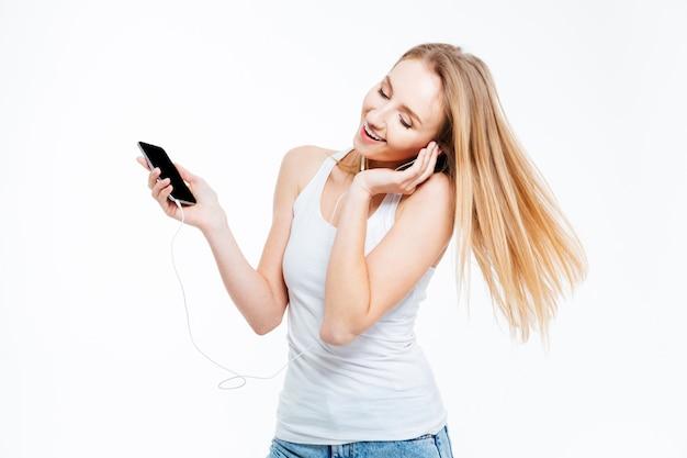 Piękna kobieta słucha muzyki w słuchawkach na białym tle