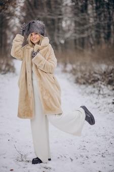 Piękna kobieta spacerująca w parku pełnym śniegu
