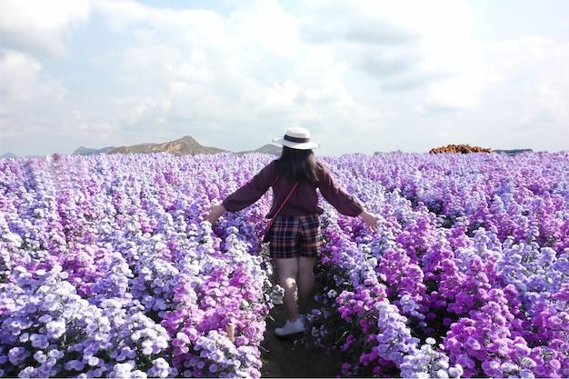 Piękna kobieta spaceruje po fioletowej plantacji kwiatów z niebieskim niebem