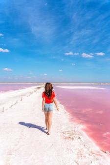 Piękna kobieta spaceruje po słonej plaży między drewnianymi kijami po słonym różowym jeziorze z błękitnym niebem