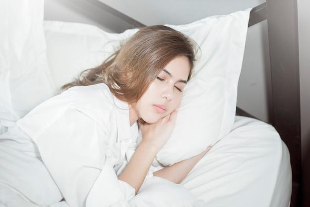 Piękna kobieta śpi na łóżku
