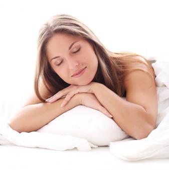 Piękna kobieta śpi w łóżku