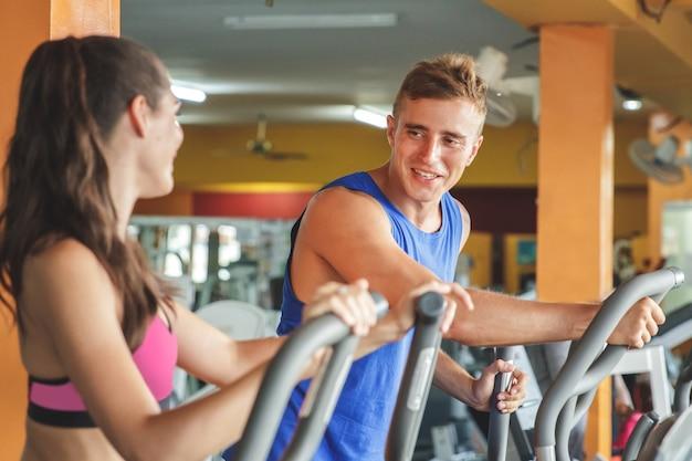 Piękna kobieta sportowa ćwiczenia na maszynie fitness i rozmawiać ze swoim partnerem
