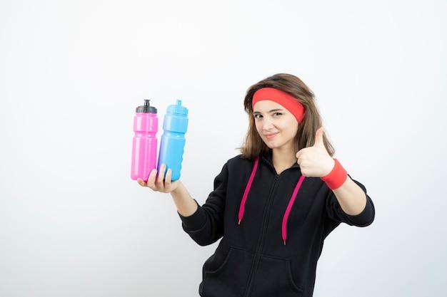 Piękna kobieta sportowa trzymając kolorowe butelki i pokazując kciuk do góry.