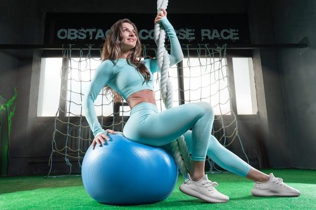 Piękna kobieta sportowy siedzi na piłce fitness