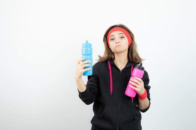 Piękna kobieta sportowy trzymając butelki z wodą na białej ścianie.
