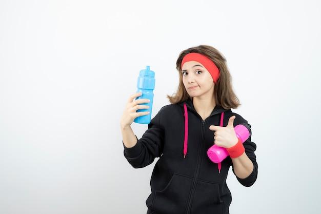 Piękna kobieta sportowy, wskazując na kolorowe butelki z wodą na białej ścianie.