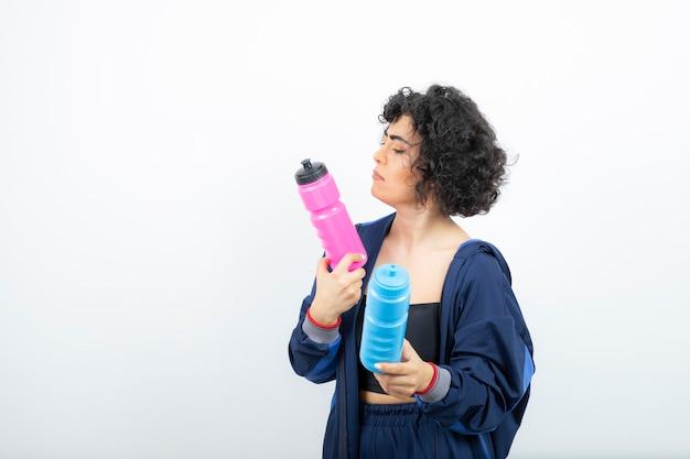 Piękna kobieta sportowy z różowym i niebieskim stojącym butelkami wody.