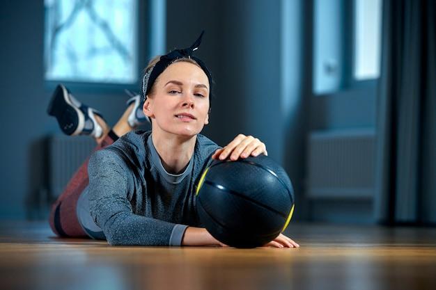 Piękna kobieta sprawny w sportowej pozowanie, leżąc na podłodze z koszykówką przed oknem w siłowni.