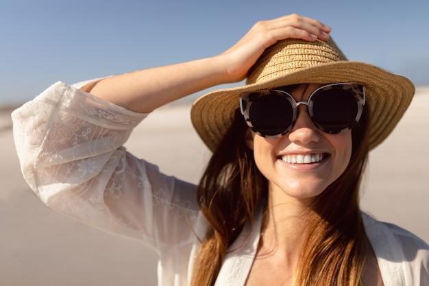 Piękna kobieta stoi na plaży w świetle słonecznym w kapeluszu i okularach przeciwsłonecznych