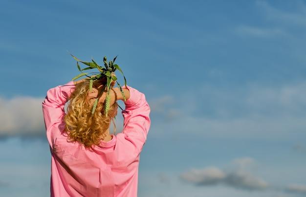 Piękna kobieta stoi plecami do ramy, w dłoniach nad głową kłosy pszenicy. błękitne niebo z chmurami, selektywne skupienie z miejscem na kopię, pomysł na baner lub tło