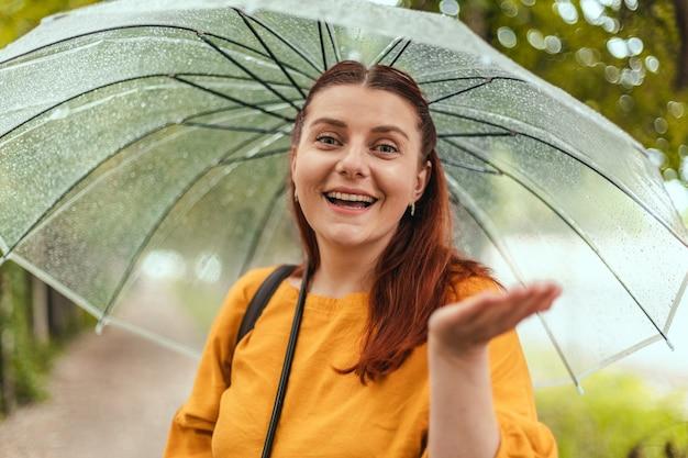 Piękna kobieta stoi pod przezroczystym parasolem i wyciąga rękę łapiąc krople...