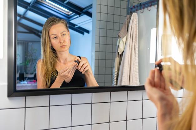 Piękna kobieta, stojąc przed lustrem w łazience, trzyma słoiczek kremu nakładającego krem nawilżający na twarz.