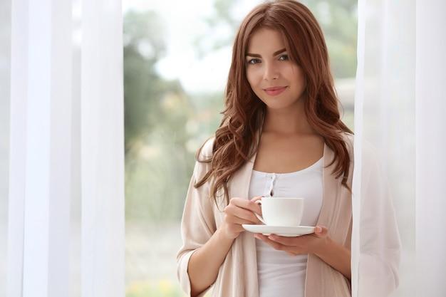 Piękna kobieta stojąc w pobliżu okna z filiżanką aromatycznej kawy
