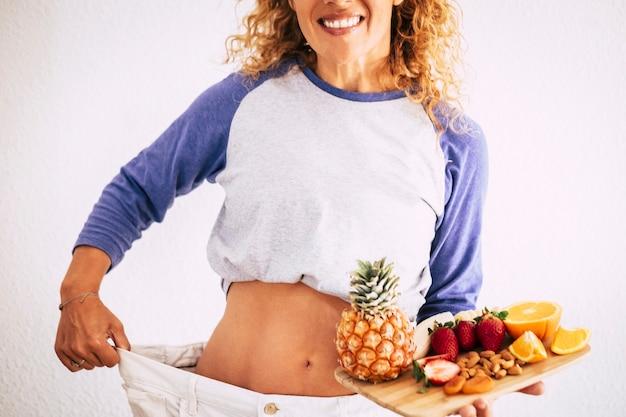 Piękna kobieta stojąca przed kamerą pokazująca swoje duże stare spodnie, aby pokazać swój sukces w stylu życia i lepiej pozostać przy sobie