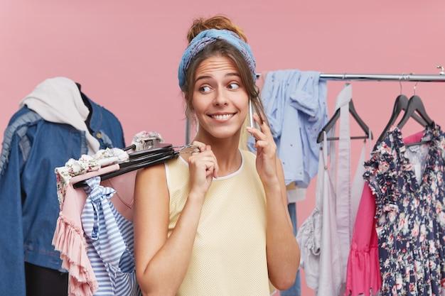 Piękna kobieta stojąca w przymierzalni, trzymając w rękach wiele wieszaków z ubraniami, dzwoniąc przez telefon