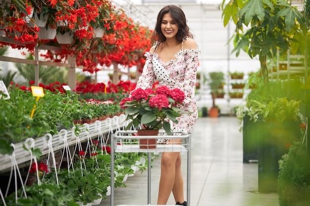 Piękna kobieta stojąca w szklarni z wózkiem na zakupy