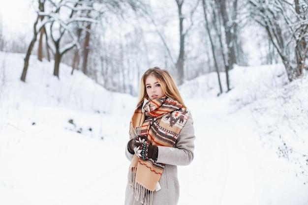 Piękna kobieta stojąca w winter park w pobliżu drzewa w stylowej odzieży vintage