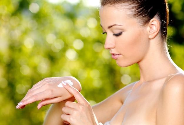 Piękna kobieta, stosując krem kosmetyczny do rąk.