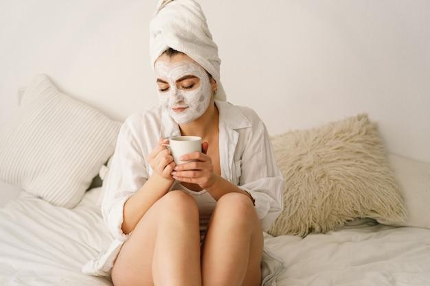 Piękna kobieta stosując maseczkę na twarz i picie herbaty w łóżku.