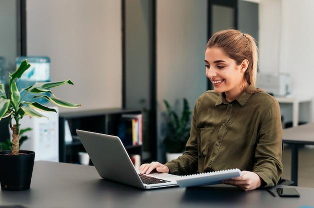 Piękna kobieta studiuje online w domu.