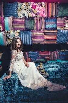 Piękna kobieta sultana ubiera biżuterię diadem w stylu orientalnym i wnętrzu