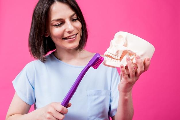 Piękna kobieta szczotkuje zęby sztucznej czaszki za pomocą dużej szczoteczki do zębów