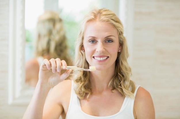 Piękna kobieta szczotkuje zęby w łazience
