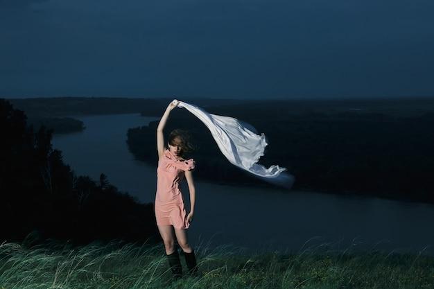 Piękna kobieta tańczy w różowej sukience z dużym białym szalem w nocy na rzece