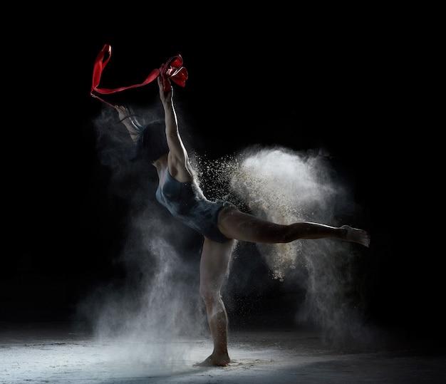 Piękna kobieta tańczy z czerwoną wstążką