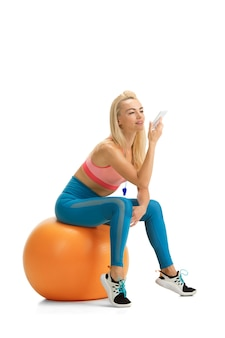 Piękna kobieta trener fitness ćwiczy na białym tle na białej ścianie