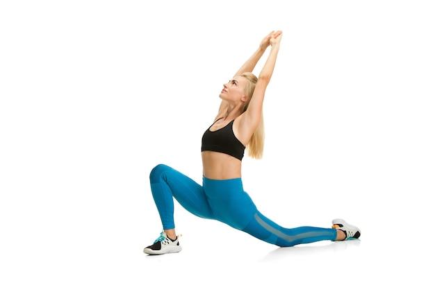 Piękna kobieta trenerka fitness ćwicząca na białym tle na białej ścianie studyjnej