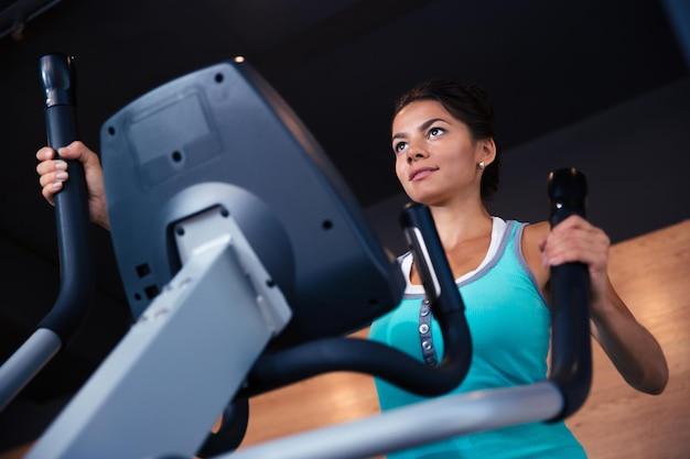 Piękna kobieta trening na maszynie do ćwiczeń w siłowni fitness