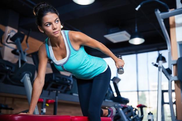 Piękna kobieta trening z hantlami na ławce w siłowni