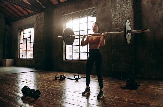 Piękna kobieta trenuje i wykonuje trening funkcjonalny na siłowni