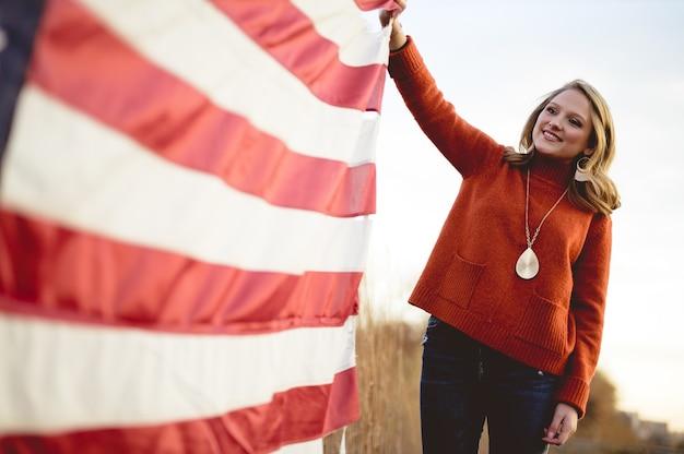 Piękna kobieta trzyma amerykańską flagę stojąc w pobliżu drzew
