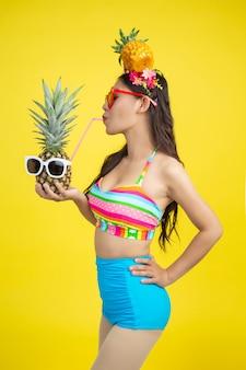 Piękna kobieta trzyma ananasa w swimsuit pozuje na kolorze żółtym