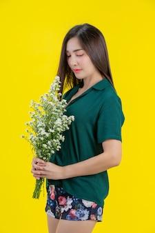 Piękna kobieta trzyma białego kwiatu