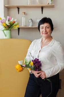 Piękna kobieta trzyma bukiet kwiatów