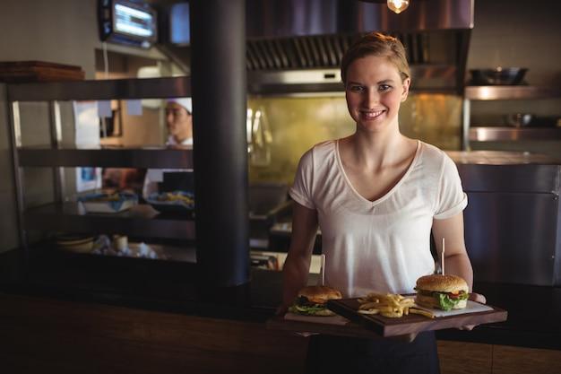 Piękna kobieta trzyma burgera i frytki na tacy w restauracji