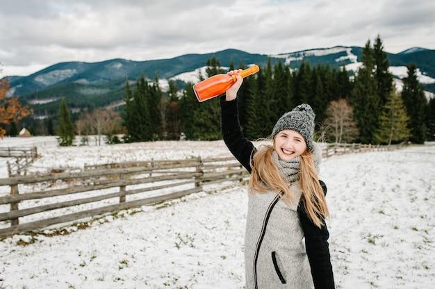 Piękna kobieta trzyma butelkę szampana na tle zimowych gór. dziewczyna w śnieżną zimę, spacer w przyrodzie. koncepcja podróży i wakacji. wakacje w sezonie zimowym.