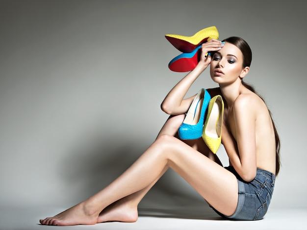 Piękna kobieta trzyma buty na obcasie.