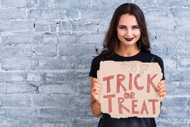 Piękna kobieta trzyma cukierek albo psikus znak