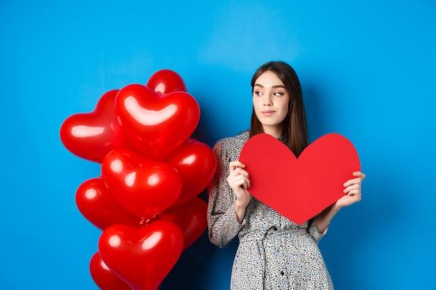 Piękna kobieta trzyma czerwone serce obok czerwonych balonów w kształcie serca