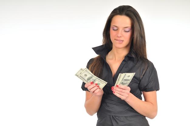 Piękna kobieta trzyma dolary w dłoniach, pełnej długości zdjęcie, na białym tle na białej ścianie
