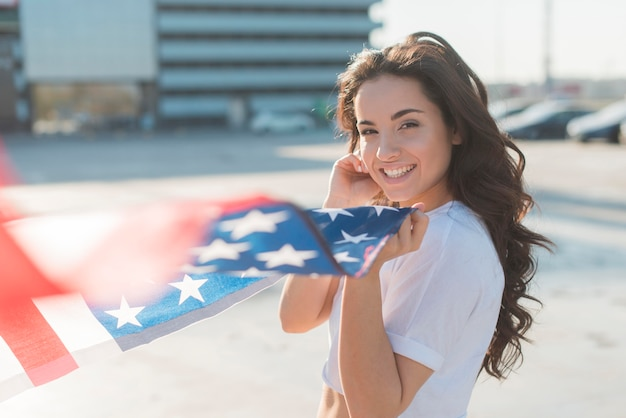 Piękna kobieta trzyma dużą usa flaga